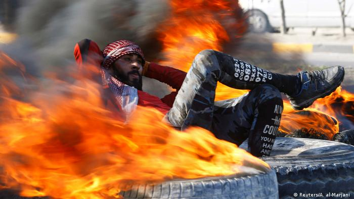 A man reclines on a tyre with his hands behind his head and foot crossed on knee in between the flames of burning tyres