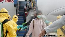 Medical officers spray Indonesian nationals with antiseptic as they arrive from Wuhan, China's center of the coronavirus epidemic, and before transferring them to the Natuna Islands military base to be quarantined, at Hang Nadim Airport in Batam, Riau Islands, Indonesia, February 2, 2020 in this photo taken by Antara Foto. Antara Foto/via REUTERS ATTENTION EDITORS - THIS IMAGE WAS PROVIDED BY A THIRD PARTY. MANDATORY CREDIT. INDONESIA OUT.