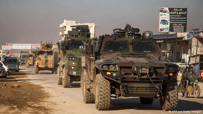 A Turkish military convoy of tanks and armored vehicles passes through the Syrian town of Dana, in the northwestern Idlib province.