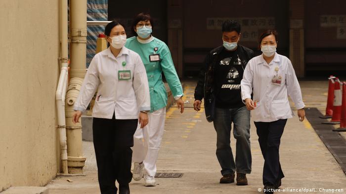 Masked nurses and janitors walk outside a hospital in Hong Kong.