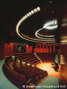 Rows of seats in a semicircle in a modern building with a grand piano at front center