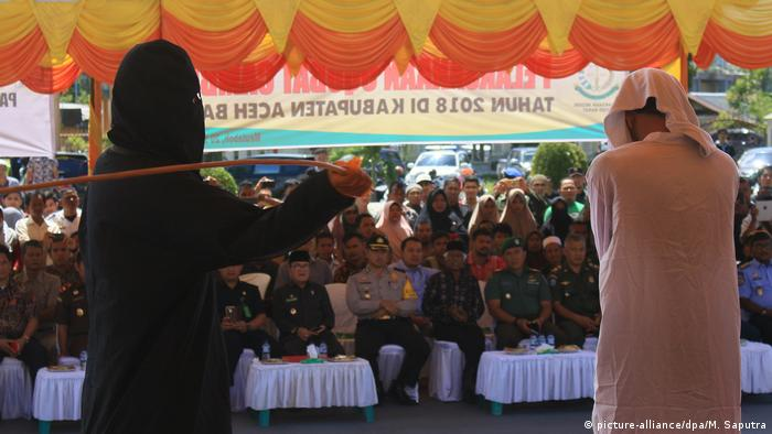 A man is caned in front of a crowd in Aceh