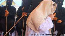 September 20, 2018 - Meulaboh, Aceh, Indonesia - A woman seen being whipped on the public stage..19 people (18 men and 1 woman) were sentenced by the Meulaboh Sharia Court by being whipped in public for sexually abusing children and gambling. the application of caning (whipping) in Aceh is carried out in public, usually carried out in front of the mosque to display the consequences of giving a deterrent effect to the perpetrators who violate Islamic Sharia. Despite criticism from the international community, until now Aceh still applies Islamic Sharia law |