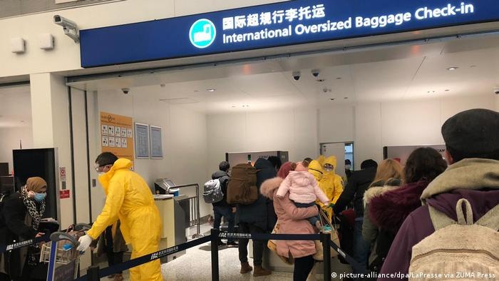 Passengers line up at check in at Wuhan airport