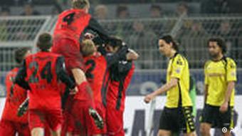 Die Eintracht (v.) feiert den Erfolg, der BVB schaut zu. (Foto: apn)
