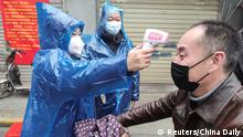 01.02.2020 *** A worker takes body temperature measurement of a man at the entrance to a residential compound following an outbreak of the new coronavirus in Wuhan, Hubei province, China February 1, 2020. Picture taken February 1, 2020. China Daily via REUTERS ATTENTION EDITORS - THIS IMAGE WAS PROVIDED BY A THIRD PARTY. CHINA OUT.