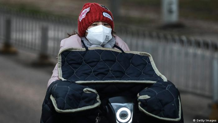 A woman wears a protective mask as she rides on a bicycle in Wuhan, China
