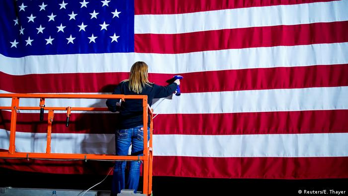 A woman steams the wrinkles from a flag