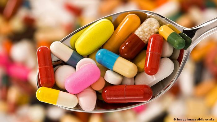Colorful pills on a spoon
