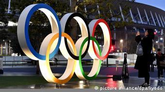 Женщина фотографирует олимпийскую символику в Токио