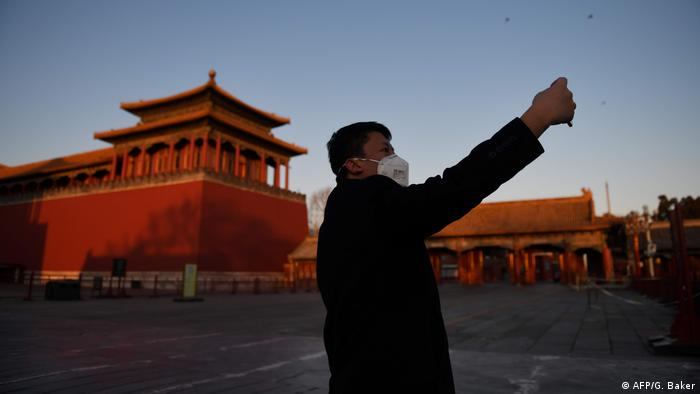 a man taking a selfie, Chinese buildings in the background (AFP/G. Baker)