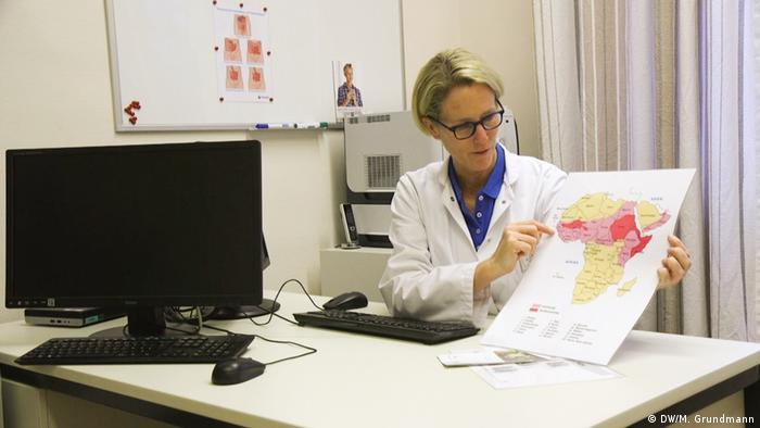 Dr. Cornelia Strunz, holding a color-coded map of Africa showing where FGM is still prevalent. In her office at the Desert Flower Center in Berlin. (DW/M. Grundmann)