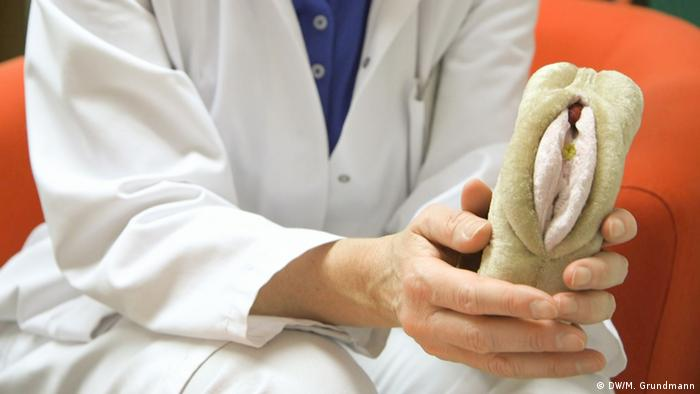 A medic holding a plastic vulva in her hand