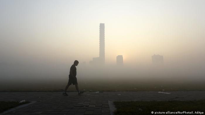 A lone figure walks through heavy smog, against the backdrop of a partially visible skyline