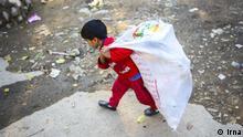 Iran Kind trägt Sack mit Abfällen