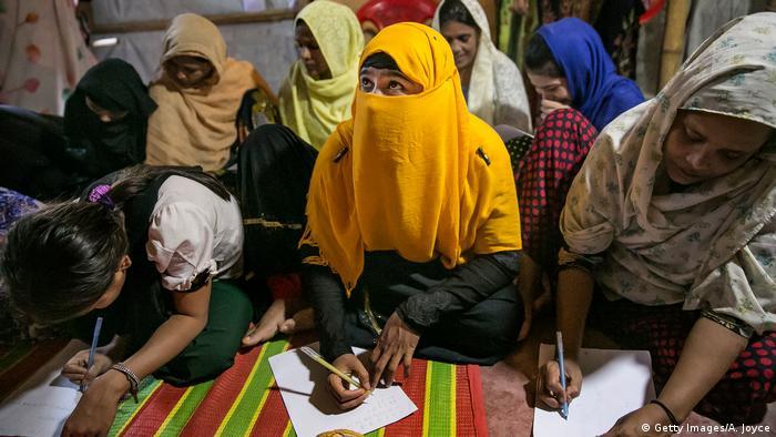 Las niñas refugiadas se sientan en el suelo y toman notas durante una clase