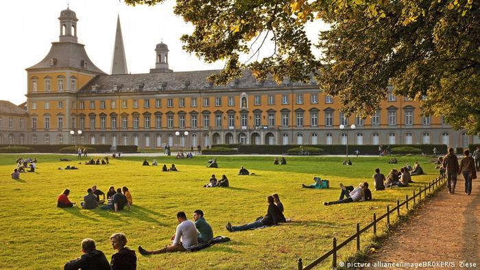 Junge Menschen sitzen auf einer Wiese vor dem schloßähnlichen gelben Hauptgebäude der Universität Bonn