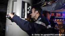 In this photograph taken at sea on July 4, 2017, French president Emmanuel Macron (C) looks through the periscope of submarine Le Terrible during a visit to the vessel. / AFP PHOTO / POOL / Fred TANNEAU (Photo credit should read FRED TANNEAU/AFP via Getty Images)