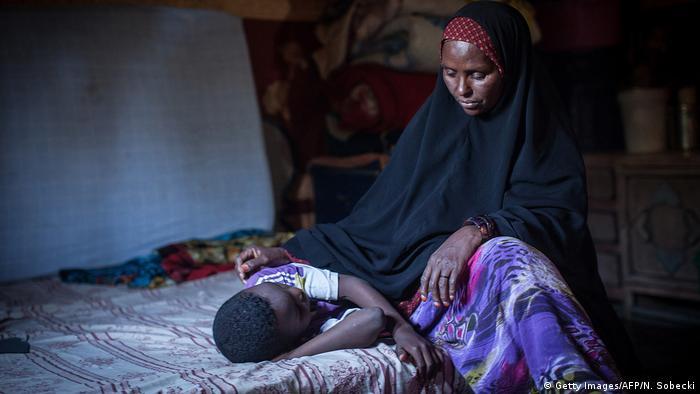 Mulher com véu islâmico sentada na cama põe a mão sobre uma jovem
