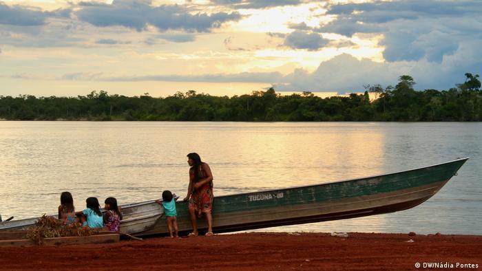 Mulher e quatro crianças juto a canoa em margem de rio