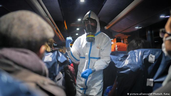 Ein polnischer Soldat in Wroclaw betritt einen Bus mit Evakuierten Patienten aus Wuhan. Er trägt einen Ganzkörperanzug und eine militärische Gasmaske mit ABC-Filter