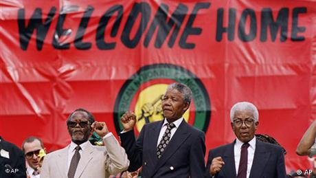 African National Congress (ANC) leadership standing from left: Oliver Tambo, president, Nelson Mandela, vice president and Walter Sisulu, internal leader give black power salutes Sunday, Dec. 16, 1990 in Johannesburg. A welcome rally was held for Tambo who returned Thursday after 30 years in exile. (AP Photo/John Parkin)