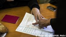 An Iranian woman presses her inked-finger on a registering paper during the parliamentary and Assembly of Experts elections at a polling station at Massoumeh shrine in the holy city of Qom, 130kms south of the capital Tehran, on February 26, 2016. Long lines formed and voting was extended as Iranians cast ballots in an election test for President Hassan Rouhani, who hopes to curb conservative dominance after a nuclear deal with world powers. / AFP / BEHROUZ MEHRI (Photo credit should read BEHROUZ MEHRI/AFP via Getty Images)