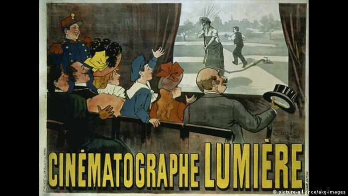 Werbeplakat für den Kinematografen der Brüder Lumière: Auf einem Bildschirm wird ein Schwarz-Weiß-Film abgespielt. Davor sitzt das Publikum, bestehend aus jungen und älteren Männern und Frauen.