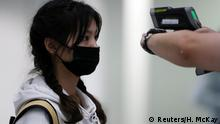 A passenger arriving into Hong Kong International Airport gets her temperature checked by a worker using an infrared thermometer, following the coronavirus outbreak in Hong Kong, China, February 7, 2020. REUTERS/Hannah McKay