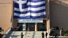 Lesbos locals unfurl massive Greek flag on the face of a state building in a bid to reclaim their island, hosting some 25,000 refugees