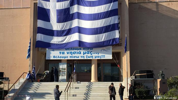 Lesbos locals unfurl massive Greek flag on the face of a state building