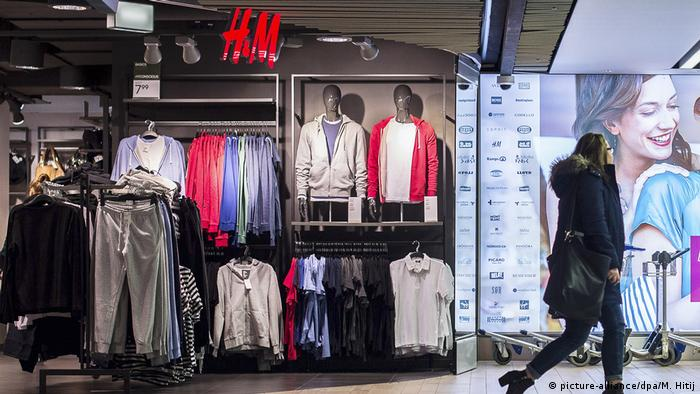 A woman walks past an H&M store where clothes are on display