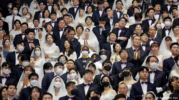 South Korean couples in mass wedding, some with masks, others without (Reuters/H. Ran)