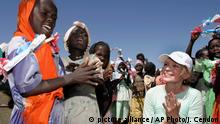 U.S. actress and UNICEF goodwill ambassador Mia Farrow sings with displaced children in Kalma refugee camp near Nyala town, Monday, Nov. 8, 2004, in south Darfur, Sudan. Farrow's visit was meant to bring attention to the hardships faced by residents of Darfur, hundreds of thousands of whom have fled their burned and looted villages. (AP Photo/Jose Cendon)  