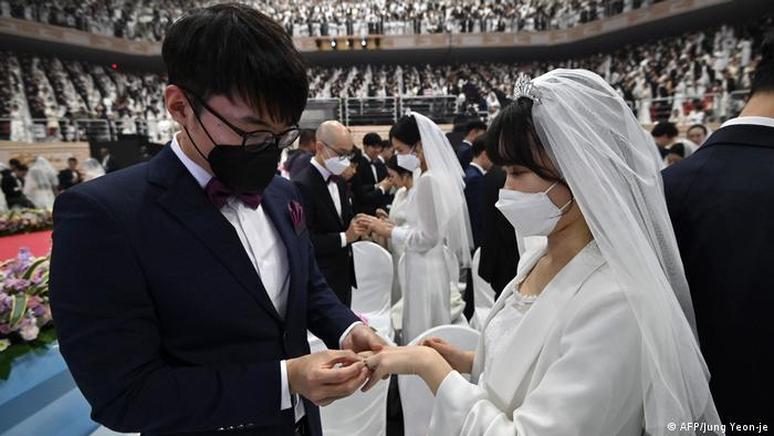 Groom puts ring on bride's hand (AFP/Jung Yeon-je)