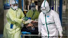 In this Thursday, Feb. 6, 2020, photo, medical workers transfer a patient in the isolation ward for 2019-nCoV patients at a hospital in Wuhan in central China's Hubei province. The number of confirmed cases of the new virus has risen again in China on Saturday, Feb. 8, 2020, as the ruling Communist Party faced anger and recriminations from the public over the death of a doctor who was threatened by police after trying to sound the alarm about the disease over a month ago. (Chinatopix via AP)
