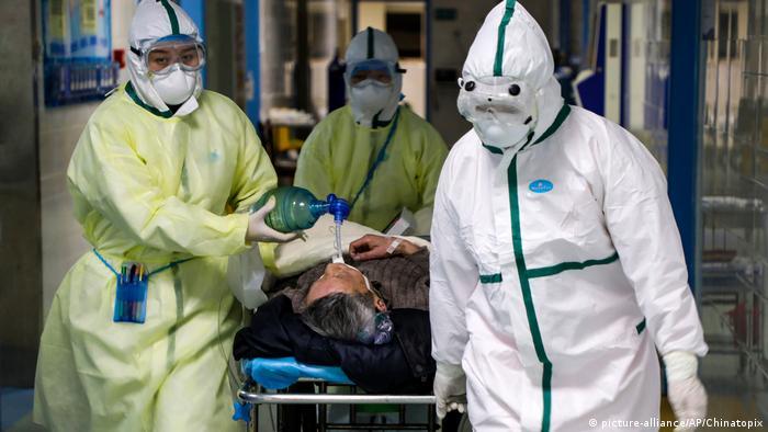 Três profissionais com roupas especiais, máscaras e óculos de proteção levam um paciente em uma maca.
