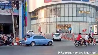 A person runs away from a shopping mall during a Thai soldier's shooting rampage in the city of Nakhon Ratchasima, Thailand