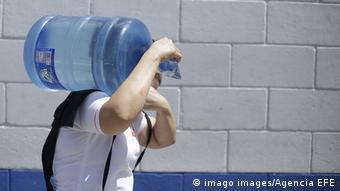 Foto de una persona cargando agua.