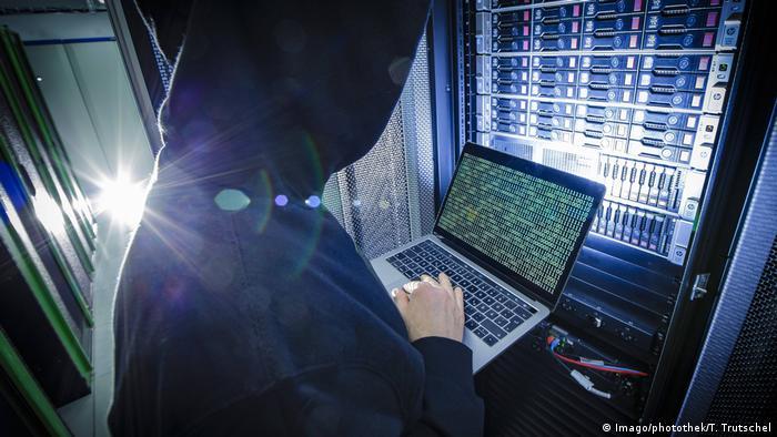 Hombre utiliza su computador para decodificar un artefacto tecnológico.