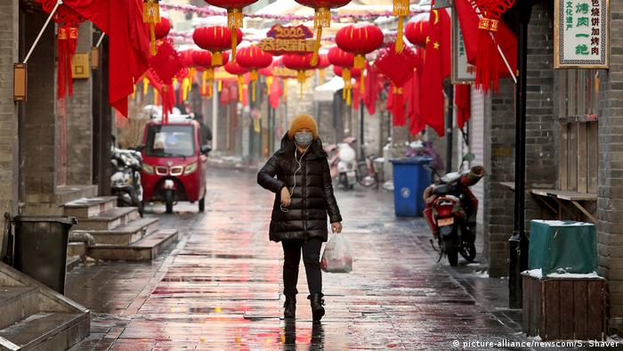 Mulher com máscara caminha em rua vazia em Pequim