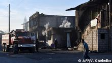 A fire engine is stationed outside a burnt out building in the village of Masanchin some 250 kilometres from Almaty on February 8, 2020. - Eight people were killed, dozens hurt and property burned during clashes between ethnic Kazakhs and members of the Dungan minority group and Hui Muslims, a group that migrated from China in the 19th Century, reports said in southern Kazakhstan, prompting concern from authorities who portray the country as a beacon of stability. (Photo by Vyacheslav OSELEDKO / AFP)