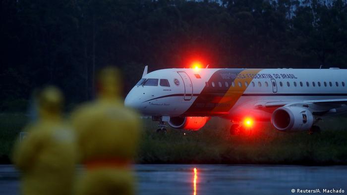Avião com luzes vermelhas em pista de pouso na penumbra, observado por duas pessoas fora de foco, vestindo macacão amarelo