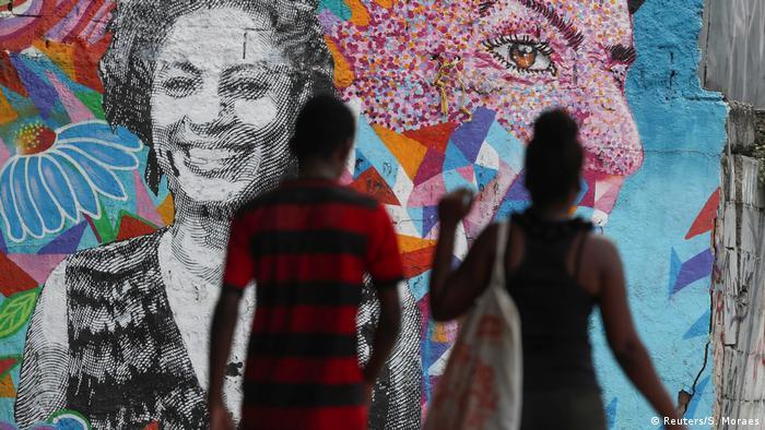 Casal passa na frente de um grafite com o rosto da vereadora Marielle Franco