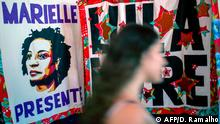 A woman walks past a poster depicting slain city councillor of the Municipal Chamber of Rio de Janeiro for the Socialism and Liberty Party (PSOL), Marielle Franco, during the celebration of the 40th anniversary of the Workers' Party (PT), in Rio de Janeiro, Brazil on February 8, 2020. (Photo by DANIEL RAMALHO / AFP)