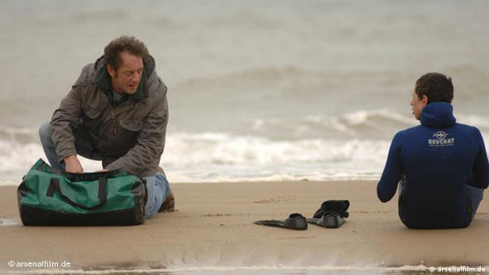 Welcome - Film scene with a man and a boy at the beach (arsenalfilm.de)
