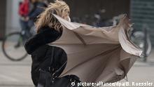10.02.2020, Hessen, Frankfurt/Main: Eine kräftige Böe hat den Regenschirm dieser Passantin vor dem Dchauspiel Frankfurt runiert. Das Sturmtief Sabine fegt noch immer mit teils sehr hohen Windgeschwindigkeiten über Deutschland. Foto: Boris Roessler/dpa   Verwendung weltweit