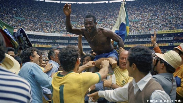 Pelé sem camisa carregado nos ombros colegas da equipe em um estádio