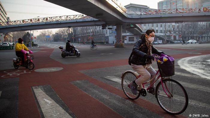 People with surgical masks ride bikes in Beijing