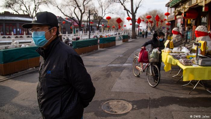 A man wearing a protective mask near a store in Beijing